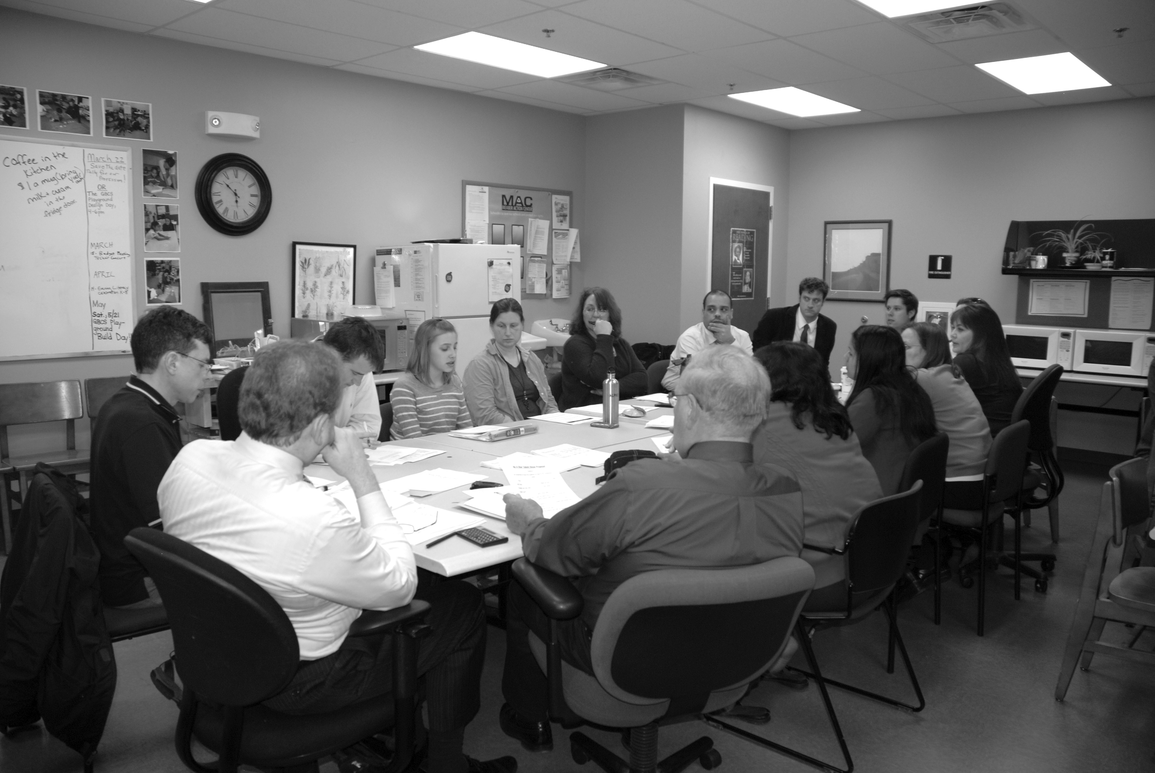 A black and white photo of adults around a table discussing something